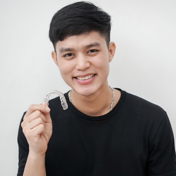 A young man smiling and holding a clear aligners