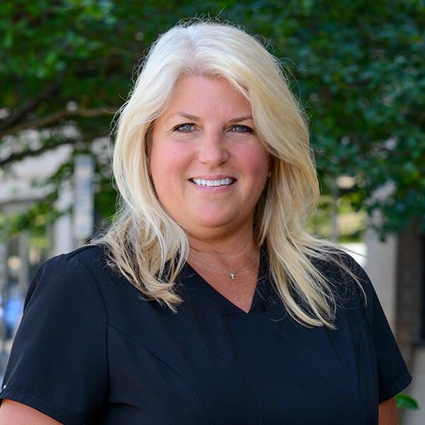 Jill smiling outside in her scrubs